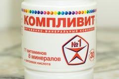 Complivit se cierra para arriba de vitaminas y de suplementos en un fondo blanco con una botella marrón Incluyendo vitamina C, vi fotos de archivo libres de regalías