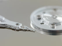 Component parts of opened hard disk drive. Macro illustration of a dismantled hard disk showing the slider and the actuator's arm and head Royalty Free Stock Photo