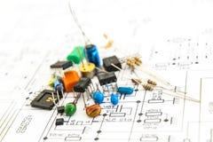 Componentes electrónicos en un fondo del diagrama esquemático. Imagen de archivo libre de regalías