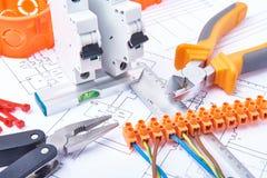 Componentes para o uso nas instalações elétricas Corte alicates, conectores, fusíveis e fios Acessórios para o trabalho de engenh imagens de stock