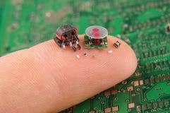Componentes pequenos da eletrônica no dedo humano imagens de stock royalty free
