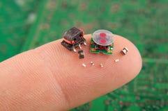 Componentes pequenos da eletrônica no dedo humano foto de stock