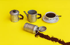 The components  of a coffee maker with alongside  the cup full. A coffee-maker of aluminium removed after filling the cup of coffee with the strip of coffee Stock Photos
