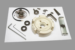 Components Of Disassembled Potentiometer. Components of a disassembled potentiometer spread out on a white board on a grey background stock image
