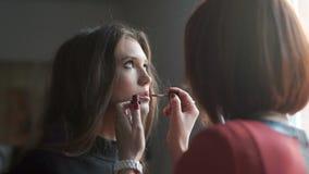 Componga al artista que hace el maquillaje para el modelo Uso del lustre del labio almacen de metraje de vídeo