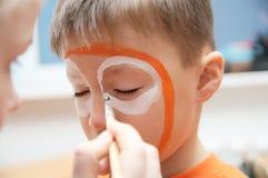 Componga al artista que hace la máscara del tigre para el niño Pintura de la cara de los niños Muchacho pintado como tigre o león Imagenes de archivo