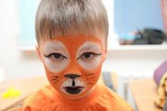 Componga al artista que hace la máscara del tigre para el niño Pintura de la cara de los niños Muchacho pintado como tigre o león Foto de archivo