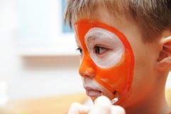 Componga al artista que hace la máscara del tigre para el niño Pintura de la cara de los niños Muchacho pintado como tigre o león Fotografía de archivo