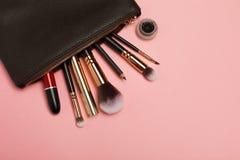 Componga el bolso con los cosméticos aislados en fondo rosado fotos de archivo libres de regalías