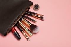 Componga el bolso con los cosméticos aislados en fondo rosado fotos de archivo