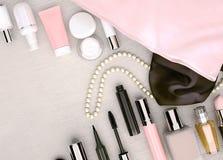 Componga el bolso, los productos de los cosméticos y los complementos localizados imagenes de archivo
