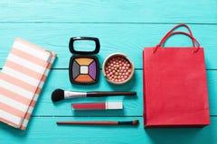 Componga el cosmético y los accesorios con el bolso rojo en fondo de madera azul Visión superior y mofa para arriba Foto de archivo