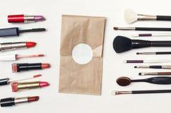 Componga el sobre del certificado, los cepillos del maquillaje y el lápiz labial fotografía de archivo libre de regalías