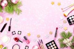 Componga i cosmetici, i presente e le decorazioni di Natale su fondo rosa artistico, spazio della copia fotografie stock libere da diritti