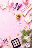Componga i cosmetici, i presente e le decorazioni di Natale su fondo rosa artistico, spazio della copia fotografie stock