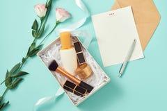 Componga il contenitore di regalo con il siero, arrossisca, spazzole, crema e rossetti all'interno immagine stock