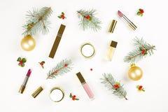 Componga il cosmetico con la decorazione di Natale sulla disposizione bianca del piano del fondo Fotografie Stock