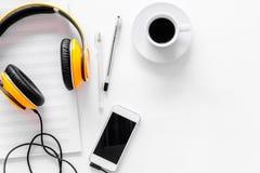 Componga la música Auriculares, notas de la música, teléfono y café en el copyspace blanco de la opinión superior del fondo imagen de archivo