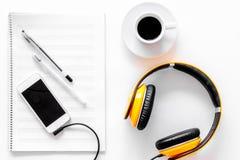 Componga la música Auriculares, notas de la música, teléfono y café en la opinión superior del fondo blanco imagen de archivo libre de regalías
