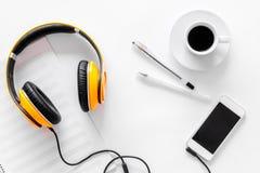 Componga la música Auriculares, notas de la música, teléfono y café en la opinión superior del fondo blanco foto de archivo