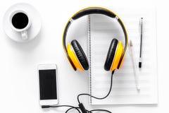 Componga la música Auriculares, notas de la música, teléfono y café en la opinión superior del fondo blanco fotos de archivo libres de regalías
