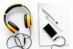 Componga la música Auriculares, notas de la música, teléfono y café en la opinión superior del fondo blanco imagenes de archivo