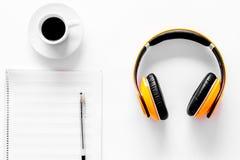 Componga la música Auriculares, notas de la música y taza de café en la opinión superior del fondo blanco imágenes de archivo libres de regalías