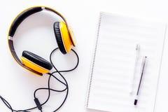 Componga la música Auriculares y notas de la música sobre la opinión superior del fondo blanco fotografía de archivo