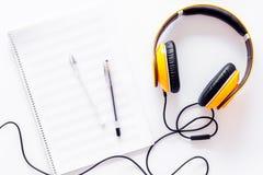 Componga la música Auriculares y notas de la música sobre la opinión superior del fondo blanco imagen de archivo libre de regalías