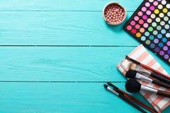 Componga las herramientas Sombreadores de ojos, cepillos del maquillaje, bolso cosmético Cosméticos en fondo de madera azul Visió Imagen de archivo libre de regalías