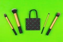 Componga le spazzole con il sacchetto della spesa nero della carta del pois sul fondo della pianta Immagini Stock Libere da Diritti