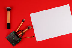 Componga le spazzole con lo strato della carta in bianco e del sacchetto della spesa su fondo rosso Immagini Stock