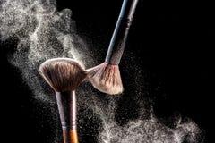 Componga le spazzole cosmetiche con polvere per arrossire esplosione su fondo nero Cura di pelle o concetto di modo immagini stock libere da diritti
