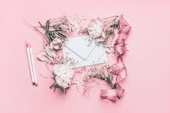 Componiendo con las peonías, el sobre, la cinta y los marcadores blancos en el fondo rosado en colores pastel, visión superior imagen de archivo libre de regalías