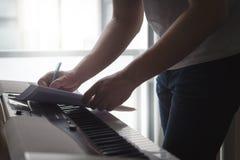 Componist en songwriter het schrijven nota's of lyrische gedichten op papier stock afbeelding