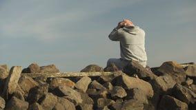 Comportamento mau de lamentação viciado comprimido, cercado com as pedras perto do lago vídeos de arquivo