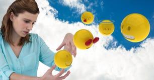 Composé de Digital de femme d'affaires avec des emojis contre le ciel nuageux Image stock