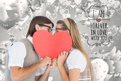 Composé de Digital des couples romantiques de ballot embrassant behing un coeur rouge Images stock
