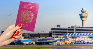Composé de Digital de main tenant un passeport BRITANNIQUE avec le terminal d'aéroport occupé Photographie stock libre de droits