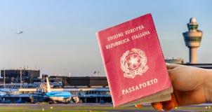 Composé de Digital de main tenant un passeport italien avec le termina occupé d'aéroport Images libres de droits