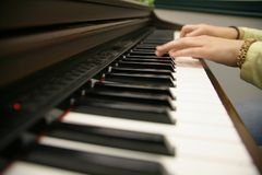 Compose. Womans hands playing on the keys of an electric piano Royalty Free Stock Photo