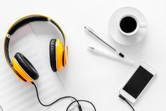 Compose music. Headphones, music notes, phone and coffee on white background top view.  stock photo