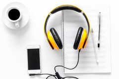 Compose music. Headphones, music notes, phone and coffee on white background top view.  royalty free stock photos