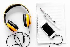 Compose music. Headphones, music notes, phone and coffee on white background top view.  stock images
