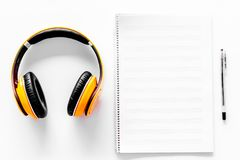 Compose music. Headphones and music notes on white background top view.  royalty free stock photo