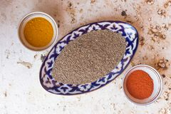 Composed bowls with various spices. Top view of ornamental bowls filled with different spices and condiments on solid surface royalty free stock image