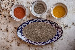 Composed bowls with various spices. Top view of ornamental bowls filled with different spices and condiments on solid surface royalty free stock photo
