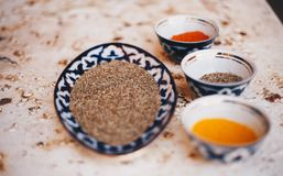 Composed bowls with various spices. Top view of ornamental bowls filled with different spices and condiments on solid surface stock photos