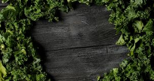Composed green salad leaves on wood. From above shot of arranged fresh lush green leaves of salad on wooden table making circle in middle stock footage