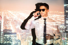 Composed man telling by phone. Double exposure of male expressing seriousness while speaking by mobile in modern metropolis projection stock photo